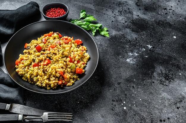 Bulgur met groenten, uien, paprika, wortelen en peterselie in een bord. zwarte achtergrond