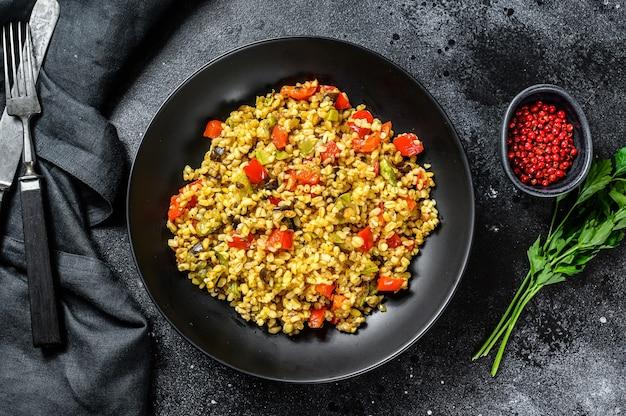 Bulgur met groenten, uien, paprika, wortelen en peterselie in een bord