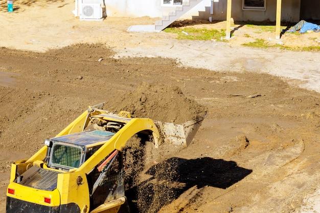 Bulldozer beweegt, nivellerend grond bij bouwwerf