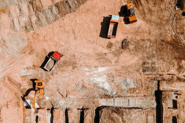 Bulldozer werkt op bouwplaats met zandantenne of bovenaanzicht bouwmachines voor graaf...