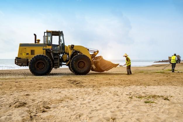 Bulldozers ruimen afval op het strand op