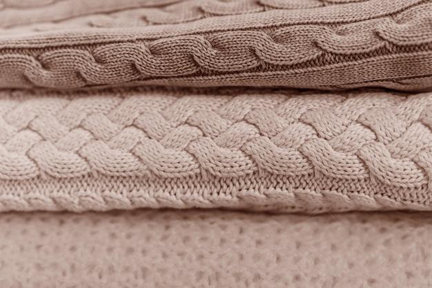 Bundel met de hand gebreide truien in pastelkleuren met verschillende breipatronen