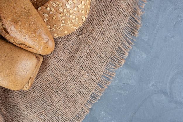 Bundel van brood op een stuk stof op marmeren achtergrond.