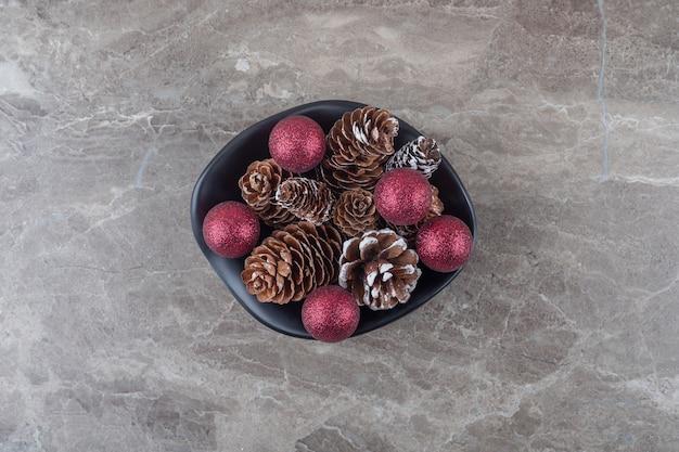 Bundel van dennenappels en kerstballen in een kom op marmeren ondergrond