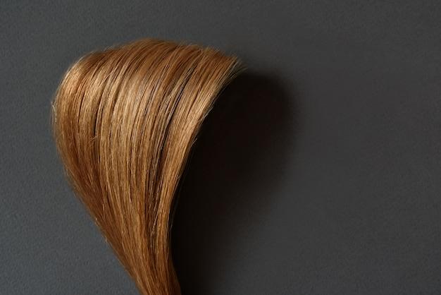 Bundel van glanzend bruin haar op grijze achtergrond. natuurlijk gezond haar.