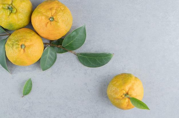 Bundel van heerlijke mandarijnen en bladeren op marmer.