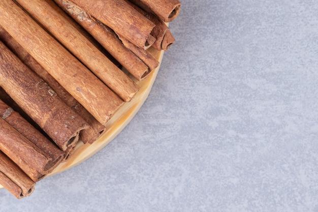 Bundel van kaneelstokjes op een kleine schotel op marmeren tafel.