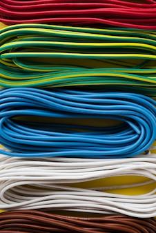 Bundel van kleurrijke elektrische kabel die in rij wordt geschikt