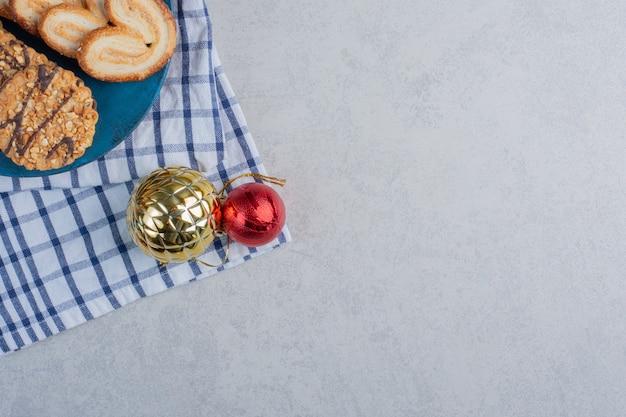 Bundel van koekjes op een blauw bord naast kerstballen op een handdoek op marmeren oppervlak
