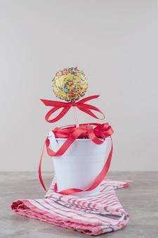 Bundel van linten en een lolly in een emmer op een handdoek op marmer