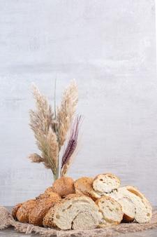 Bundel van met sesam bedekte, gesneden broodbroden met tarwestengels op marmer.