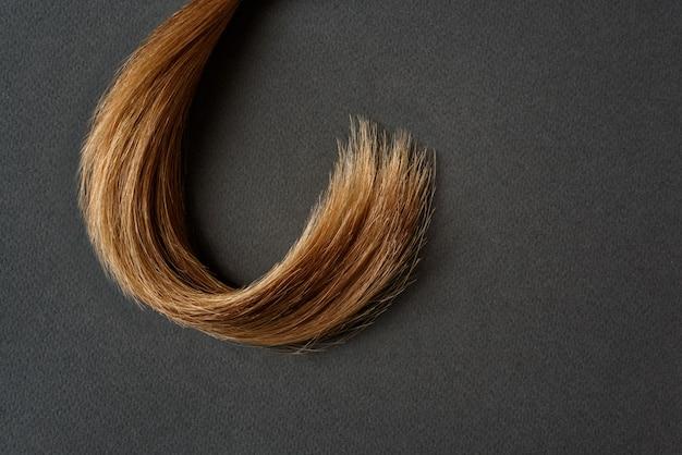Bundel van natuurlijk bruin haar op grijze achtergrond. haarverzorging concept. detailopname