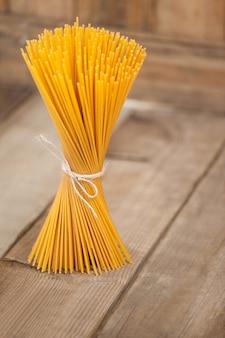 Bundel van rauwe spaghetti gebonden met touw op houten achtergrond