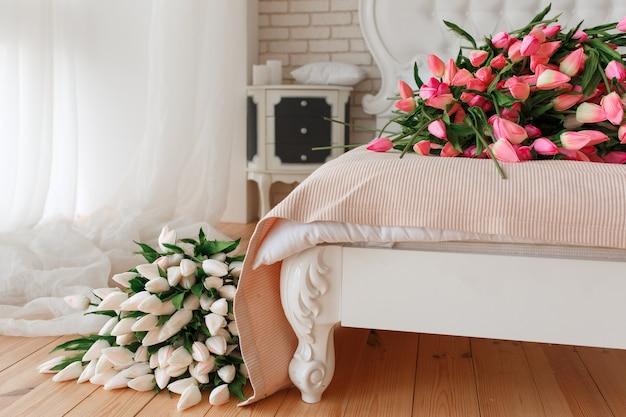 Bundel van tulpen op bed in hotelflat.