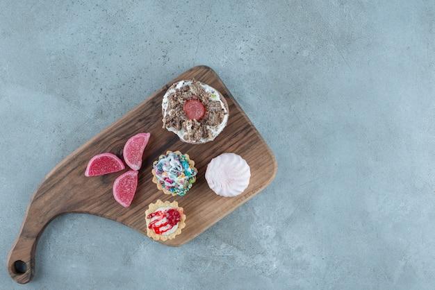 Bundel van verschillende gebakjes en marmelades op een houten bord op marmeren achtergrond. hoge kwaliteit foto