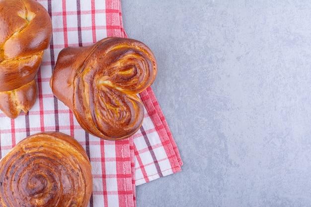 Bundel van zoete broodjes gerangschikt op een handdoek op een marmeren oppervlak