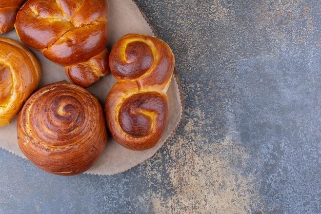 Bundel van zoete broodjes op een houten bord op marmeren oppervlak