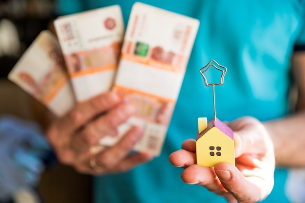 Bundels biljetten van vijfduizend russische roebel en een huis
