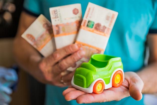 Bundels biljetten van vijfduizend russische roebel en een speelgoedauto