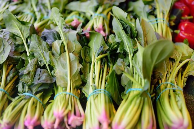 Bundels van verse groene spinazie op landbouwer landbouwmarkt