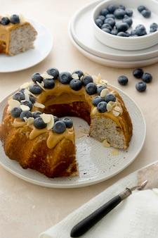 Bundtcake met pindakaasglazuur. gezonde suiker glutenvrije cake met chiazaadjes gedecoreerd met bosbessen en amandelschilfers.
