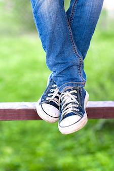 Bungelende hangende vrouwelijke benen van een jonge meisjesvrouw in jeans en oude tennisschoenen staken met zonlicht op groen gras en bomenachtergrond aan.