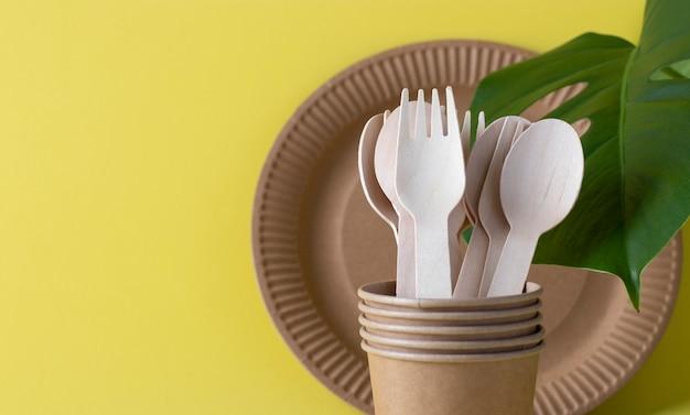 Bunner milieuvriendelijk wegwerpservies op een gele ondergrond. houten vorken en lepels in een papieren beker met papieren bord. geen afvalconcept met exemplaarruimte.