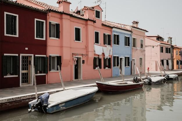 Burano, venetië, italië - 2 juli 2018: panoramisch uitzicht op felgekleurde huizen en waterkanaal met boten in burano, het is een eiland in de lagune van venetië. mensen lopen en rusten op straat