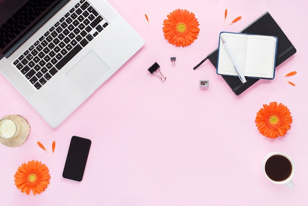 Bureau aan huis. vrouwelijke werkruimte met laptop, telefoon, pen, kaars, koffiemok, zwart dagboek met oranje bloemen en bloemblaadjes op roze achtergrond. plat lag, bovenaanzicht. fashion blog-look.