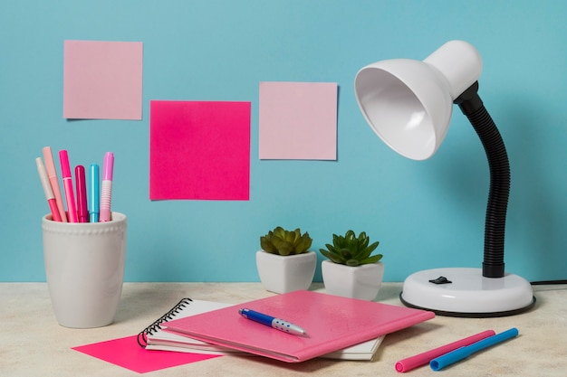 Bureau-arrangement met roze items en planten