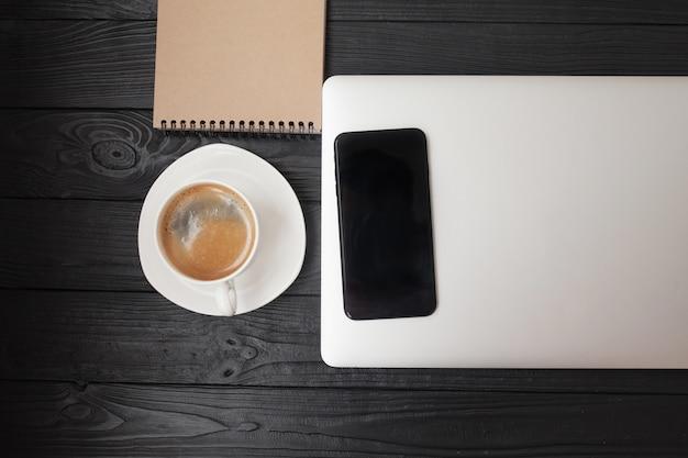 Bureau - laptop computer en koffiekop op houten textuur en achtergrond met exemplaarruimte.