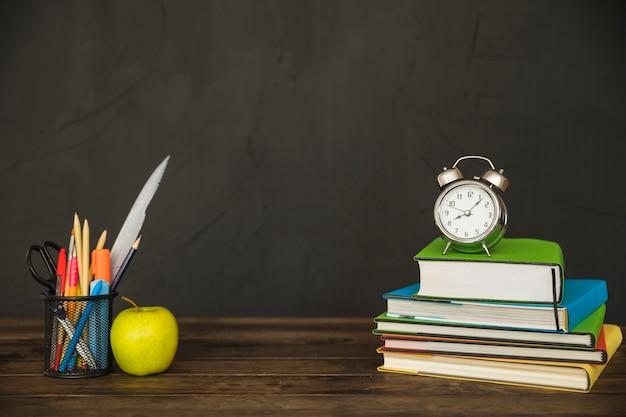 Bureau met boeken, briefpapier en klokken