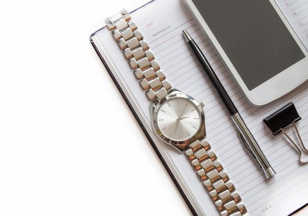 Bureau met een dagboek, smartphone, pen op een notitieblok, herenpolshorloge. bovenaanzicht