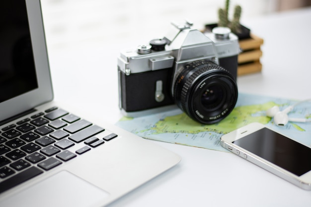 Bureau met een notebook, telefoon, camera, kaart en het plannen van een reis