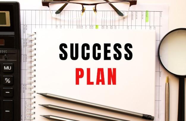 Bureau met financiële documenten, vergrootglas, rekenmachine, glazen. kladblok-pagina met de tekst succesplan. uitzicht van boven. bedrijfsconcept.