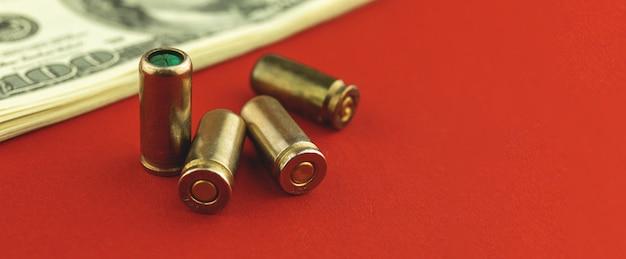 Bureau met geld en kogel voor pistool, criminele en corruptie fotobanner met kopieerruimte