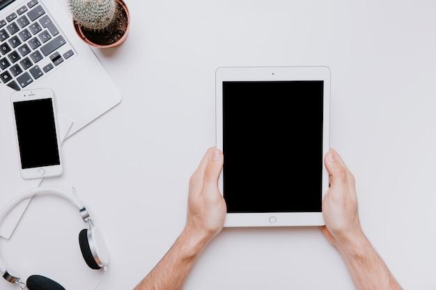 Bureau met handen die tablet houden