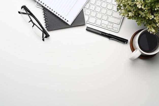 Bureau met koffiekopje, notebook, bril, draadloos toetsenbord en kopieerruimte.