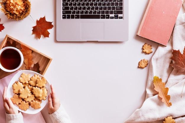 Bureau met laptop, koffiekopje, koekjes, boek en herfstbladeren. bovenaanzicht