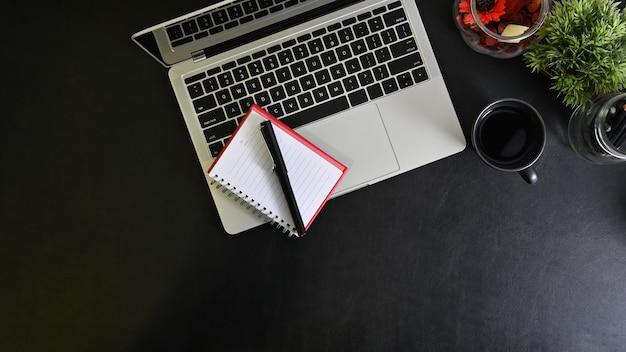 Bureau met laptop, notebookpapier, koffie met pen op zwarte lederen tafel.