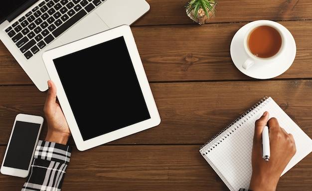 Bureau met laptop, smartphone, tablet, kopje koffie en schrijfblok