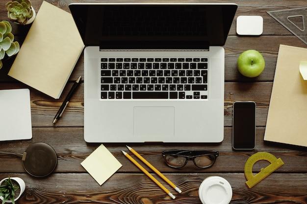 Bureau met laptopcomputer, leveringen en groene appel, bovenaanzicht