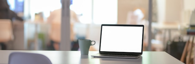Bureau met leeg scherm laptop en koffiekopje in glazen scheidingsruimte