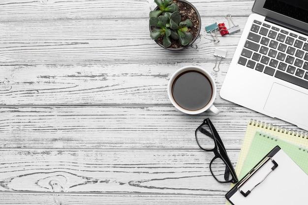 Bureau met lege kladblok, laptop en kantoorbenodigdheden bovenaanzicht
