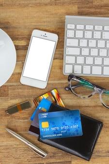 Bureau met mobiele telefoon en portemonnee met plastic kaarten, kopieer ruimte op een leeg scherm