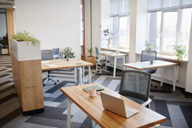 Bureau met mokplanner en geopende laptop in een leeg coworkingcentrum in de open ruimte