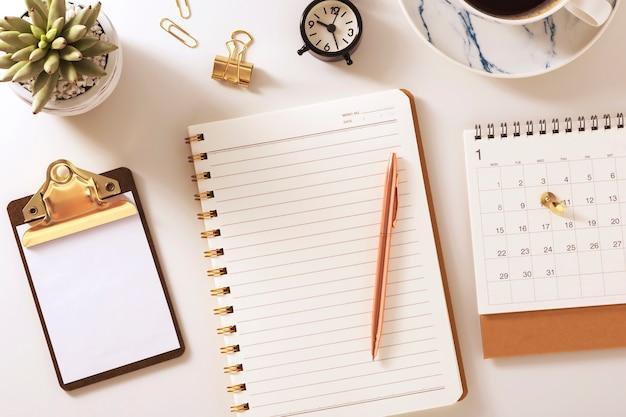 Bureau met notebook, kalender, klok en plant