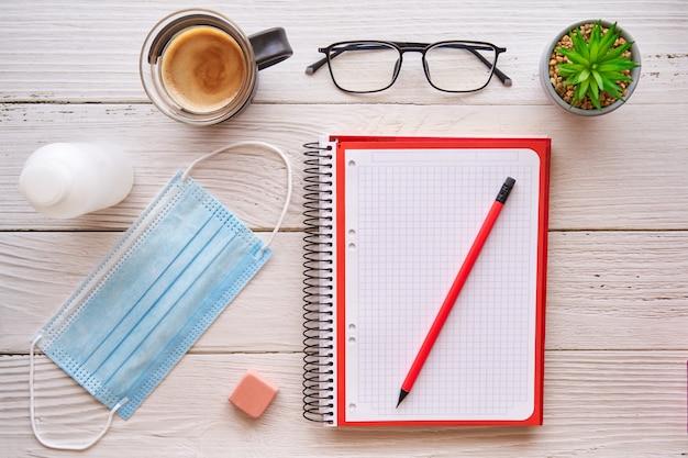 Bureau met notebook, potlood, koffie en masker concept van bescherming tegen het covid-virus.
