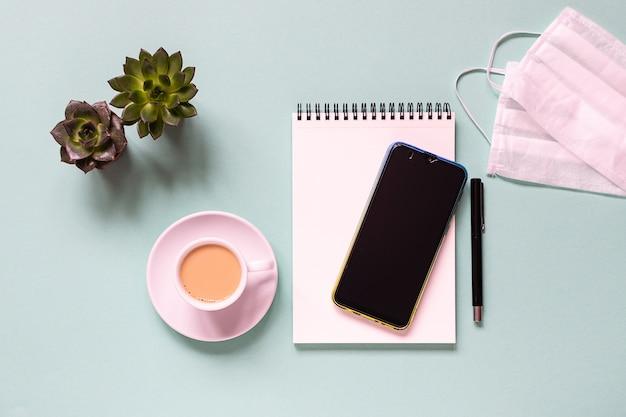 Bureau met smartphone, kopje koffie en beschermend gezichtsmasker