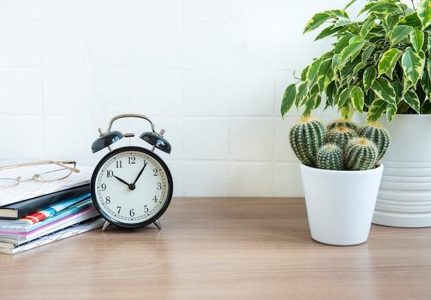 Bureau met stapel notitieblokken, wekker, kantoorbenodigdheden en kamerplanten